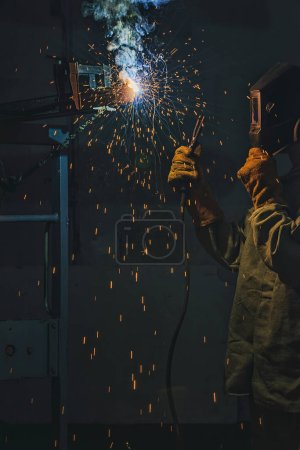 selective focus of welder in protection mask working with metal at factory