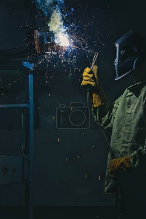 Photo for Side view of manufacture worker welding metal with sparks at factory - Royalty Free Image