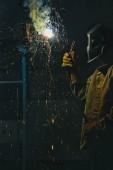 travailleur au masque de protection métallique à l'usine de soudure