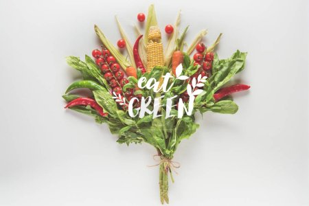 "bouquet of corn cob, spinach, basil, cherry tomatoes and chili peppers isolated on white with ""eat green"" lettering"