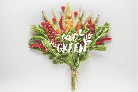 Photo pour Bouquet d'épi de maïs, épinards, basilic, tomates cerises et piments isolées on white avec «manger vert» inscription - image libre de droit