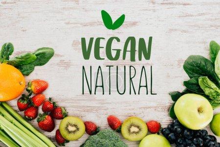 """Foto de Vista superior de fresas orgánicas dispuestas, frutas y verduras en tablero de madera con inscripción """"vegano natural"""" - Imagen libre de derechos"""
