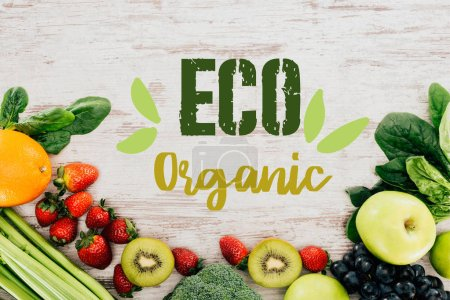 "top view of arranged organic strawberries, vegetables and fruits on wooden tabletop with ""eco organic"" lettering"