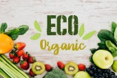 """top view of arranged organic strawberries, vegetables and fruits on wooden tabletop with """"eco organic"""" lettering"""