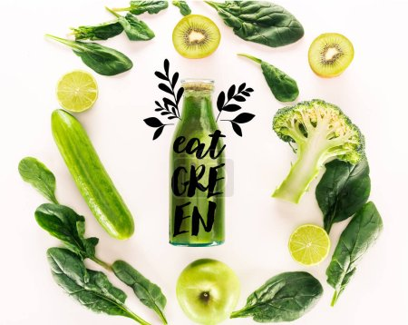 "flat lay with detox drink and various organic food isolated on white with ""eat green"" lettering"