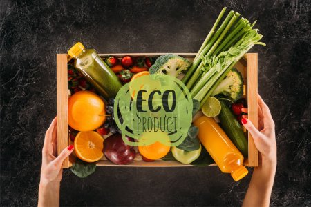 """Photo for Partial view of woman holding wooden box with healthy vegetables, fruits and detox drinks with """"eco product"""" lettering - Royalty Free Image"""