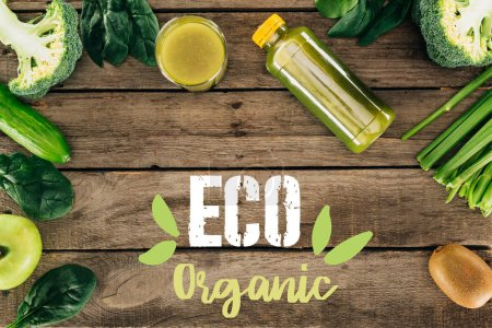 "flat lay with detox drink and various organic food on wooden surface with ""eco organic"" lettering"