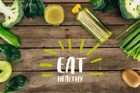 "flat lay with detox drink and various organic food on wooden surface with ""eat healthy"" lettering"