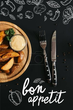 "top view of baked potatoes with sauce on wooden board and fork with knife on black with ""bon appetit"" lettering"