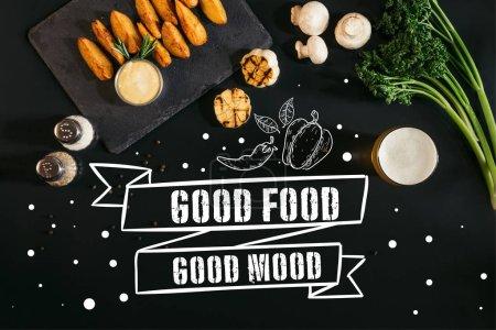 Photo pour Vue de délicieuses pommes de terre au four avec sauce, des épices et des verre de bière sur fond noir avec de dessus «bonne nourriture - bonne humeur» inspiration - image libre de droit