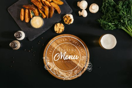 """wooden board with """"healthy menu"""" lettering in seal, glass of beer and baked potatoes with sauce and spices on black"""