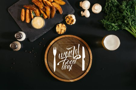 planche de bois avec l'inscription «world food day» avec fourchette et couteau, verre de bière et les pommes de terre cuites au four avec la sauce et des épices sur fond noir