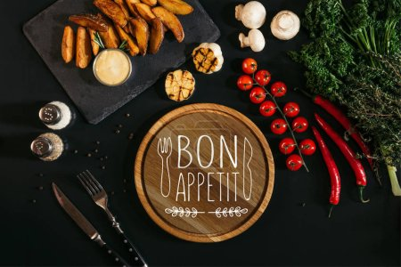 """top view of wooden board  with """"bon appetit"""" lettering, vegetables and baked potatoes on black"""