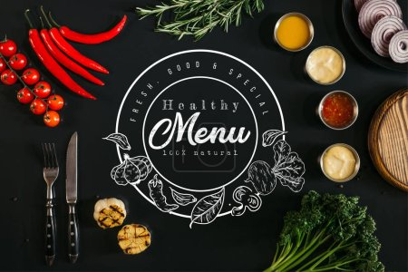"top view of various sauces, grilled garlic, fork with knife and fresh vegetables with herbs on black background with ""healthy menu"" lettering in seal"
