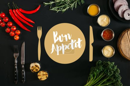 "top view of various sauces, grilled garlic, fork with knife and fresh vegetables with herbs on black background with ""bon appetit"" lettering"