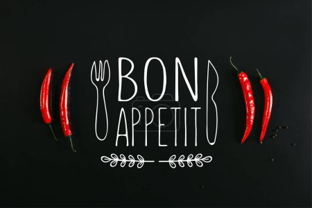 "top view of red chili peppers and peppercorns on black background with ""bon appetit"" lettering with fork and knife"