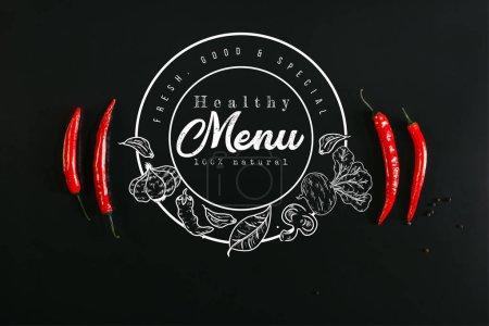 """Photo pour Vue du dessus des piments rouges et des grains de poivre sur fond noir avec inscription """"menu santé"""" dans le sceau - image libre de droit"""