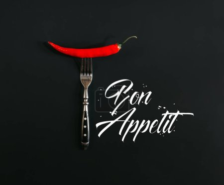 """Photo for Red hot chili pepper on fork on black with """"bon appetit"""" lettering - Royalty Free Image"""