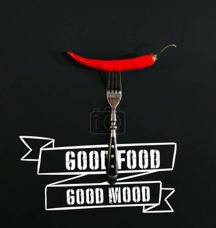"red hot chili pepper on fork on black with ""good food - good mood"" inspiration"