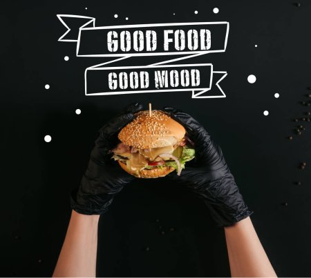 Photo pour Recadrée coup de mains dans les gants maintenant délicieux burger avec la Turquie, légumes et vinaigrette César sur noir avec «bonne nourriture - bonne humeur» inspiration - image libre de droit