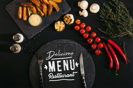 "top view of slate board with ""delicious menu restaurant"" lettering and fork and knife, baked potatoes, spices and vegetables on black"
