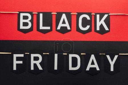 Photo pour Vendredi noir lettrage sur drapeau guirlandes sur fond rouge et noir - image libre de droit