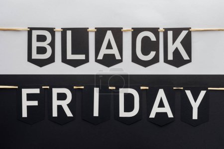 black friday lettering on flag garlands on black and white background