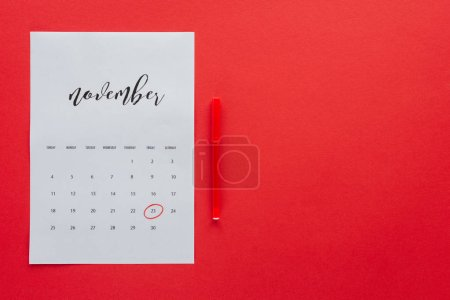 top view of calendar for November and marker isolated on red with copy space, black friday concept