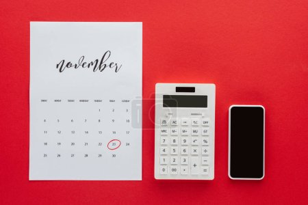 top view of calendar for November, calculator and smartphone isolated on red, black friday concept