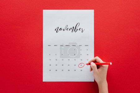 partial view of woman writing black friday in calendar for November isolated on red