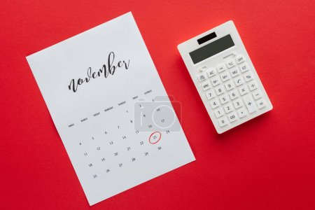 top view of calendar for November and calculator isolated on red, black friday concept