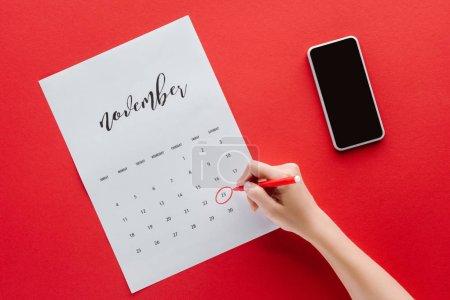 Photo pour Vue recadrée de femme écrivant vendredi noir dans le calendrier pour Novembre isolé sur rouge avec smartphone - image libre de droit