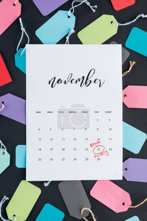 top view of november calendar with black friday sign on colorful sale tags