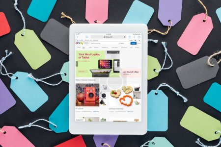 top view of digital tablet with ebay website on screen lying on colorful sale tags