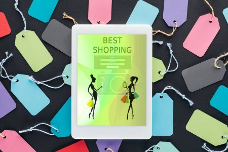 top view of digital tablet with best shopping on screen lying on colorful sale tags
