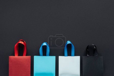 top view of colorful shopping bags on black background with copy space for black friday
