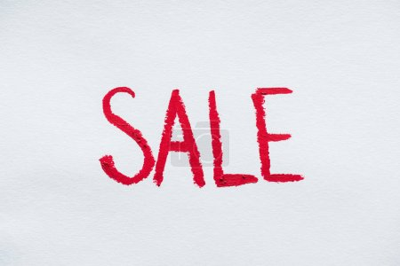 sale symbol written with red lipstick on white
