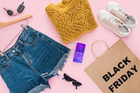 Photo pour Vue de dessus des vêtements à la mode, smartphone avec shopping sac app et papier avec signe vendredi noir - image libre de droit
