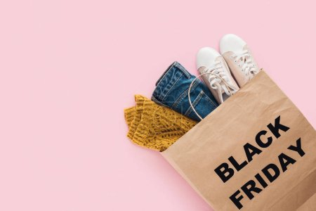 top view of trendy clothes in shopping bag with black friday sign isolated on pink