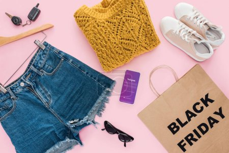 top view of trendy clothes, smartphone with instagram app and shopping bag with black friday sign