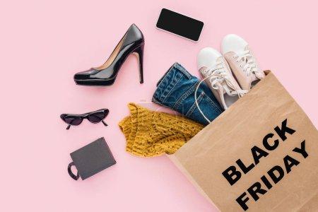 Photo pour Plat couché avec des vêtements dans un sac à provisions avec panneau noir vendredi isolé sur rose - image libre de droit