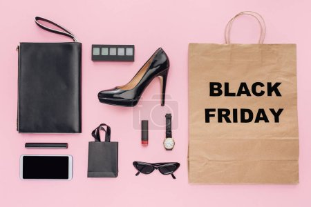 flat lay with accessories and shopping bag with black friday sign isolated on pink