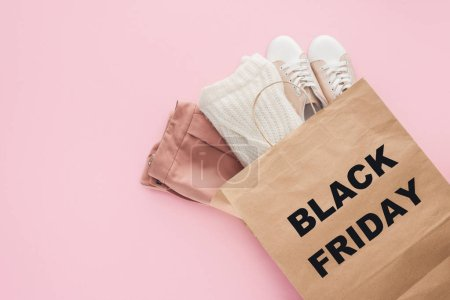top view of clothes in shopping bag with black friday symbol isolated on pink
