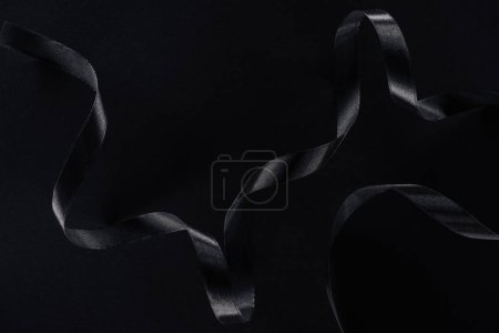 top view of black glossy ribbon on black background