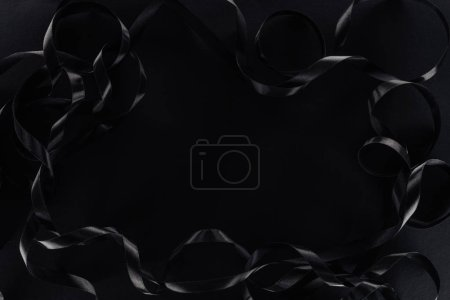top view of glossy ribbons on black background with copy space for black friday