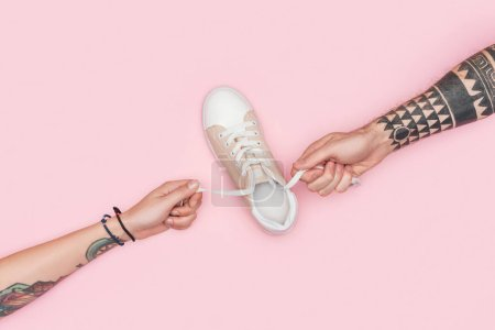 partial view of tattooed people holding laces of sneaker isolated on pink