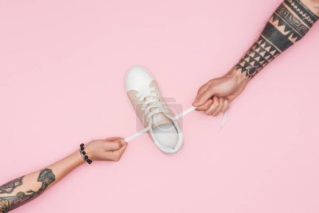 Photo for Cropped view of tattooed shopaholics pulling sneaker isolated on pink - Royalty Free Image