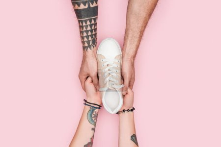 cropped view of tattooed couple holding one sneaker isolated on pink