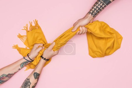 partial view of tattooed shopaholics pulling yellow scarf isolated on pink