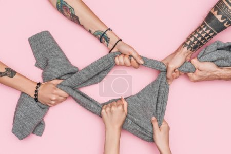 cropped view of shopaholics pulling grey scarf isolated on pink